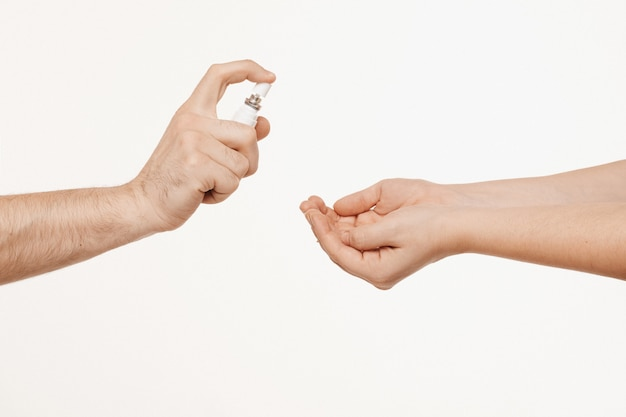 Two pairs hands holding sanitizer spray and using it. hygiene and antibacterial protection concept. covid-19, coronavirus concept. healthcare concept.