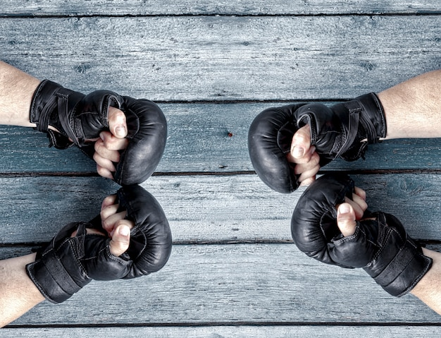 Two pairs of human hands in black leather boxing gloves facing each other