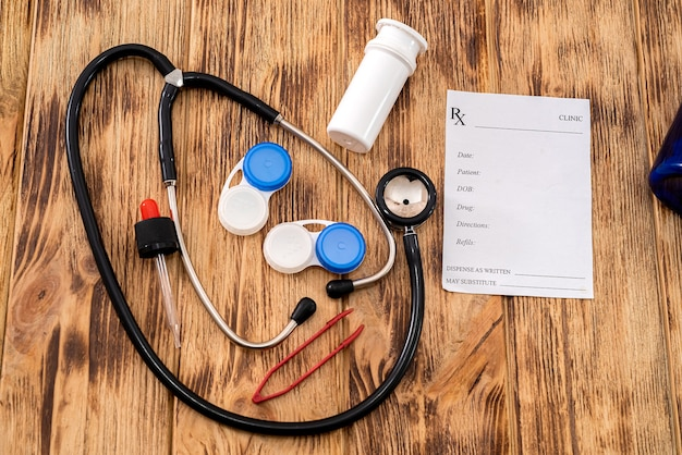 Two pairs of lenses with a stethoscope and a prescription from a doctor spread out on the table. medicine concept