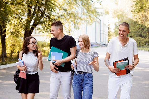 大学の学習者である2組の友人が、休憩中に学生のキャンパスでコミュニケーションを取ります。