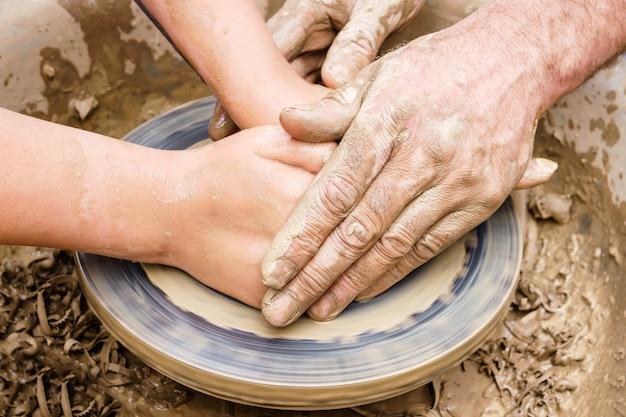 男性と女性、または老いも若きも、2組の手がろくろの上に粘土製品を作ります