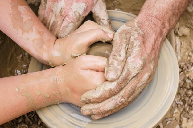 男性と女性、または老いも若きもろくろの粘土からの2組の手