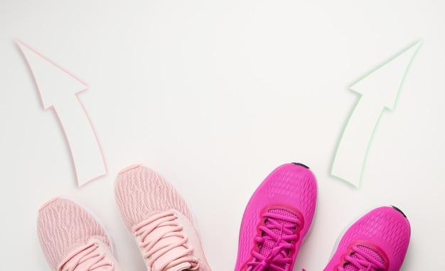 ピンクのテキスタイルスニーカーの2つのペアは反対方向に向けられています。喧嘩と意見の違いの概念、異なる人生の道と興味、上面図