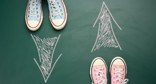 두 쌍의 섬유 운동화는 녹색 배경에 서로 마주보고 있습니다. 운동 방향의 불일치, 사고의 차이의 개념