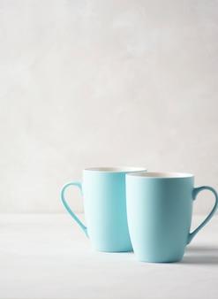 두 개의 옅은 파란색 머그잔이 회색 콘크리트 테이블에 서 있습니다.