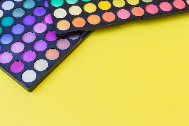 Two palette colorful eye shadow on yellow background