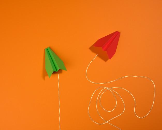 주황색 배경, 최적화의 개념, 목표 달성, 특별한 생각에 다른 이동 궤적을 가진 두 개의 종이 비행기. 복잡한 것은 간단합니다
