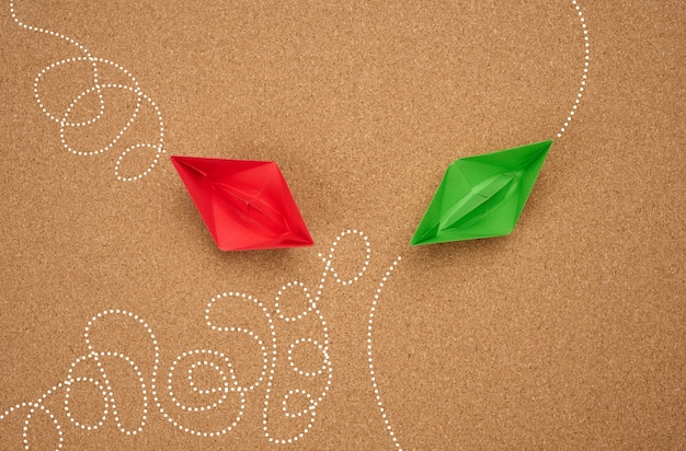 Two paper boats with different trajectory on a brown background. the concept of optimal problem solving, achieving goals in different ways, smart and capable employee