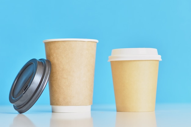 Two paper coffee cups on a blue
