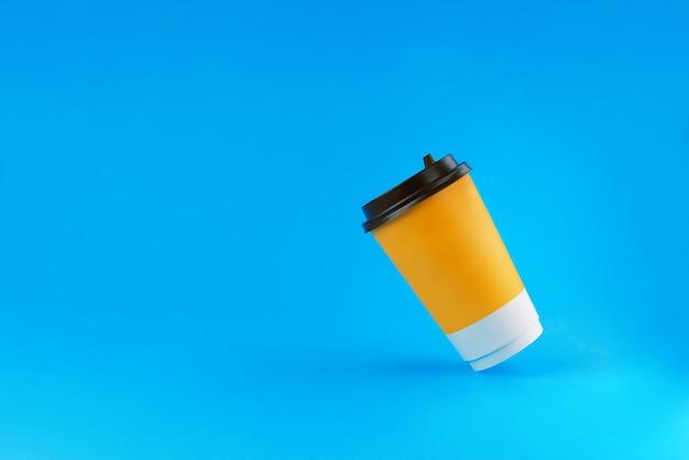 青い背景の上の2つの紙のコーヒーカップ