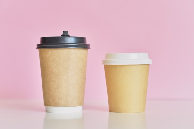 Two paper coffee cups on pink background