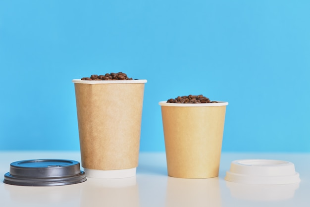 Two paper coffee cups with coffee beans on blue background