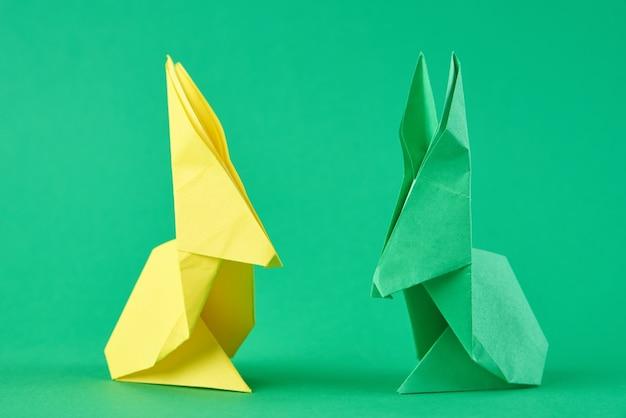 緑の上の2つの紙のカラフルな折り紙イースターウサギ
