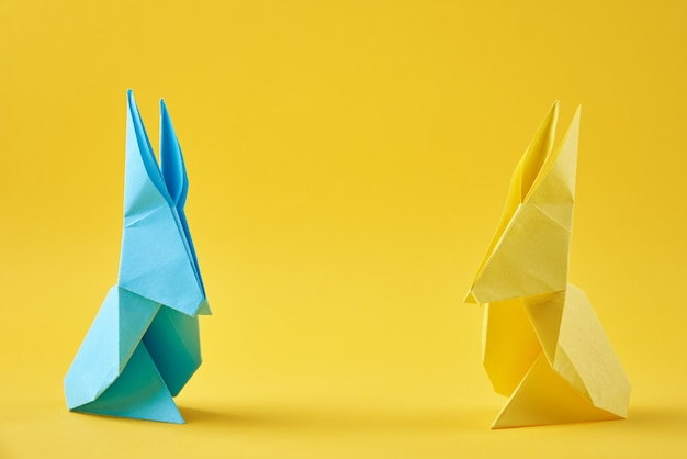Two paper colorful origami easter rabbits on a yellow surface