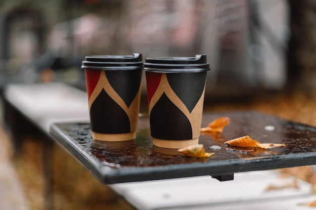 Two paper cups of coffee on a wet autumn table.