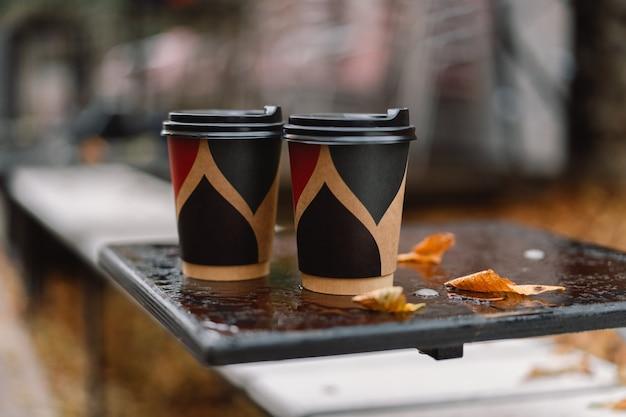 濡れた秋のテーブルにコーヒー2杯。