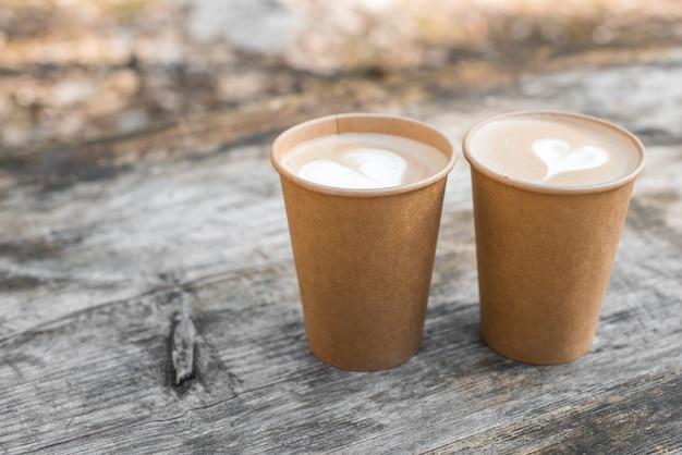 ハート型のラテアートとコーヒーの2つの紙コップ