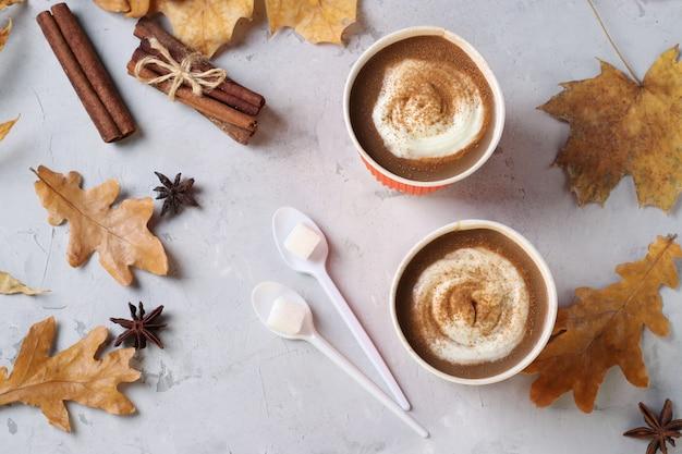 秋の葉と灰色のテーブルにおいしいカボチャラテとスパイスの2つの紙コップ。上面図。閉じる。
