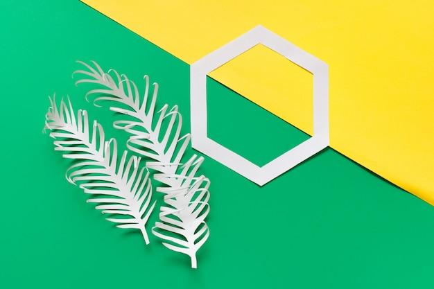 Две бумажные перья и шестиугольник на желто-зеленый