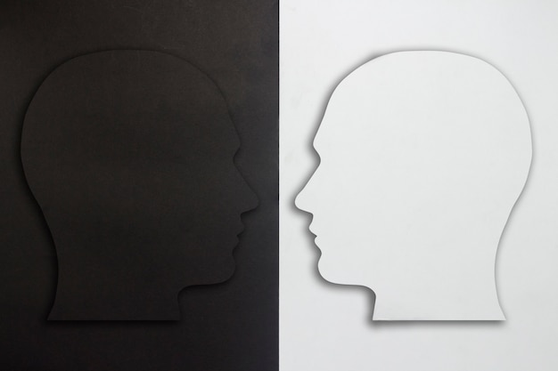 Two paper heads, black and white on a black and white background. the concept of a split personality, different opinions, dispute, war. flat lay, top view.