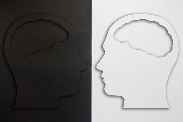 Две бумажные головы с мозгом силуэт, черный и белый на черно-белом фоне. понятие раздвоения личности, разные мнения, спор, война. плоская планировка, вид сверху.