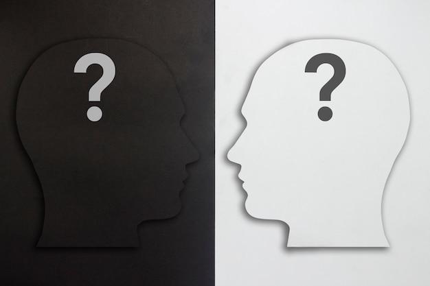 Две бумажные головки с вопросительным знаком, черный и белый на черно-белом фоне. понятие раздвоения личности, разные мнения, спор, война. плоская планировка, вид сверху.