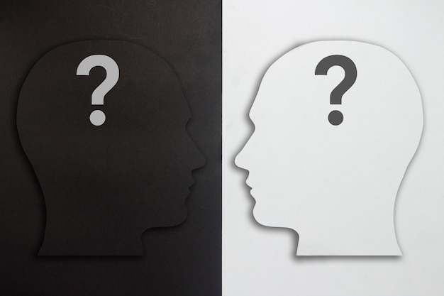 Two paper heads with a question mark, black and white on a black and white background. the concept of a split personality, different opinions, dispute, war. flat lay, top view.