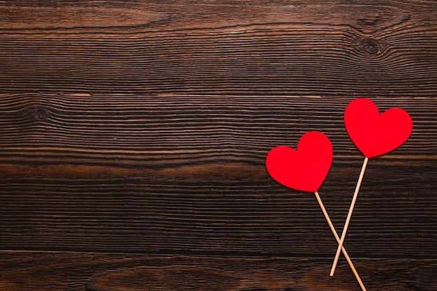 暗い木製の背景に分離されたスティック上の2つの紙のハート。温かいフラットレイを祝う上面図。バレンタインデーとクリスマスのコンセプト。コピースペース。