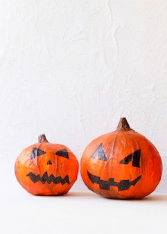 Two paper jack-o-lanterns on table