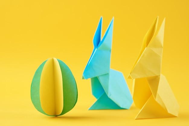 2つの紙の折り紙イースターウサギと黄色の着色された卵