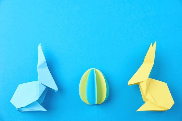 2つの紙の折り紙イースターウサギと青の色の卵