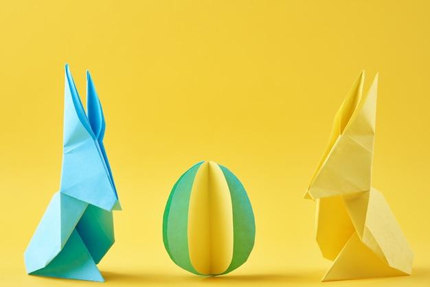 두 종이 접기 esater 토끼와 노란색 벽에 색된 달걀. 부활절 축 하 개념