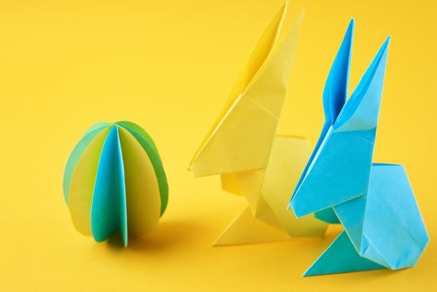 黄色い壁に2匹の紙の折り紙esaterウサギと色付きの卵。イースターのお祝いのコンセプト