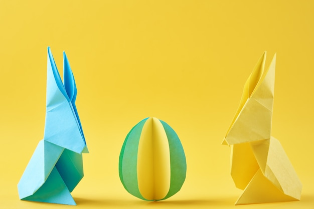 Two paper origami esater rabbits and colored egg on a yellow wall. easter celebration concept