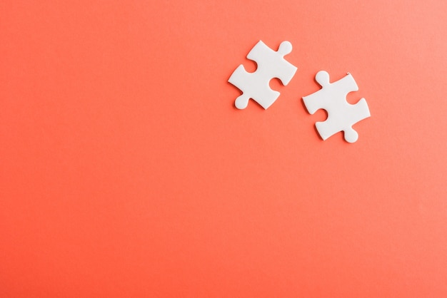 Two paper plain white jigsaw puzzle game last pieces for solve