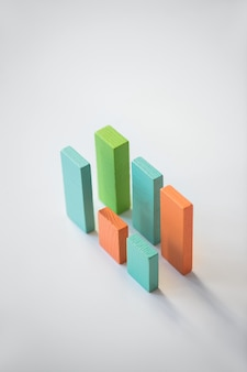 青、オレンジ、緑の平らな木製のレンガの2つの平行線は、白い背景の上に分離して財務チャートを形成します