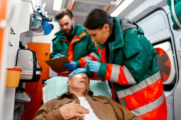 Два фельдшера осматривают учеников пожилого человека, лежащего на каталке в современной машине скорой помощи, и просматривают записи пациента.