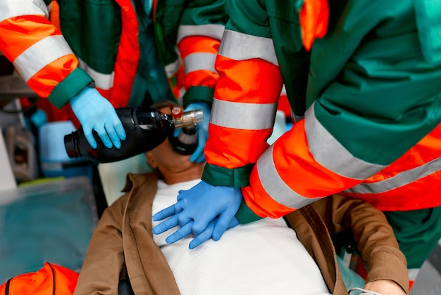 Two paramedics are resuscitating a senior lying on a gurney in an ambulance by performing chest compressions and connecting to a ventilator.