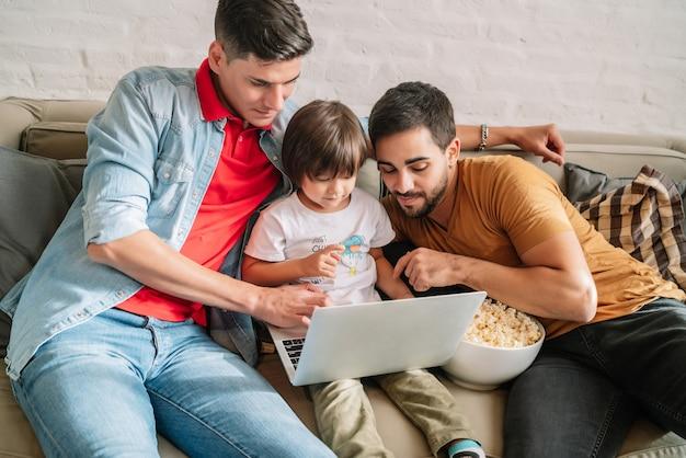 Двое родителей и их сын наслаждаются временем вместе во время просмотра фильма на диване у себя дома. семейное понятие.
