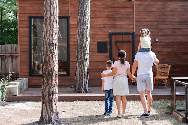 두 부모와 두 자녀는 꿈의 목조 주택을 보고 여름 방학을 위해 마을을 떠났고 딸은 아빠의 어깨에 앉아 있습니다