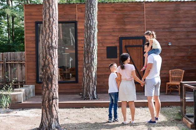 Двое родителей и двое детей, стоя во дворе возле деревянного дома, дочка сидит у папы на плечах, общаются и радуются выбору места для отдыха.