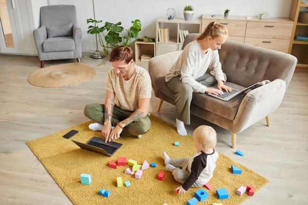 랩톱 컴퓨터를 사용하고 집에서 온라인으로 작업하는 두 부모는 아들이 바닥에 장난감을 가지고 노는 동안
