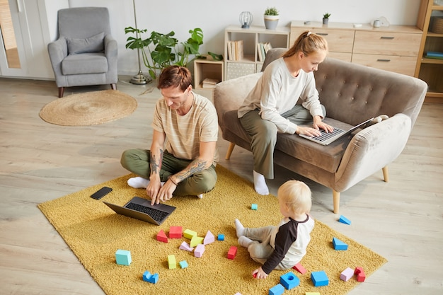 Two parents using laptop computers and working online at home while their son playing with toys on the floor