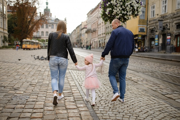 Two parents with a small daughter walk along the streets of the old city.