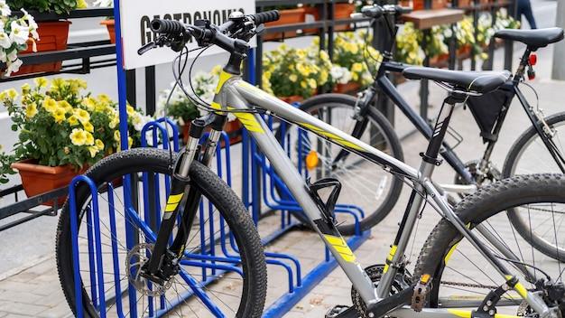 Due biciclette parcheggiate in una strada vicino a una strada, fiori