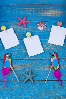 Two parrots, starfish, shells and note paper on a blue wooden background