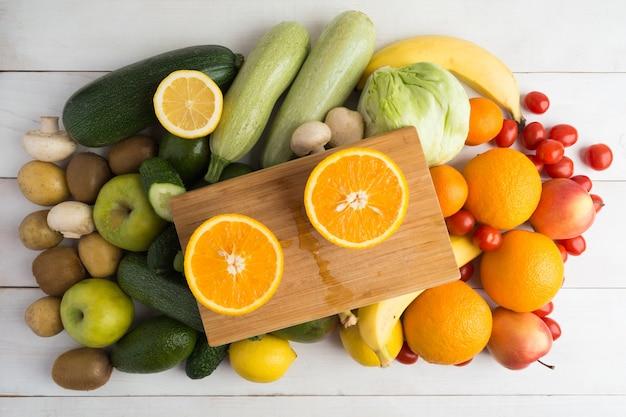 ボード上のオレンジの2つの部分と他の果物と野菜