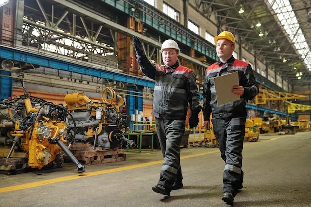 헬멧을 쓴 두 파트너가 기계 공장을 걷고 작업에 대해 논의합니다.