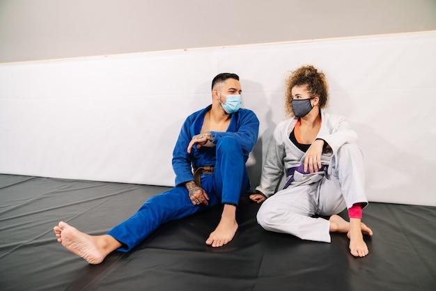 Two partners in martial arts like judo wearing kimono sitting on the floor mat talking and laughing with their face masks on due to the coronavirus