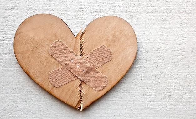 Две части разбитого деревянного сердца, скрепленные нашивкой. концепция прощения, обновления отношений и исцеления